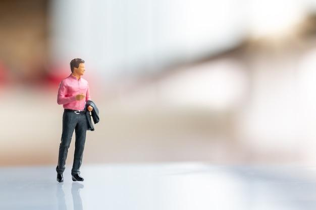 Miniatuurmensen: zakenman die zich op lege ruimte voor tekst bevindt Premium Foto