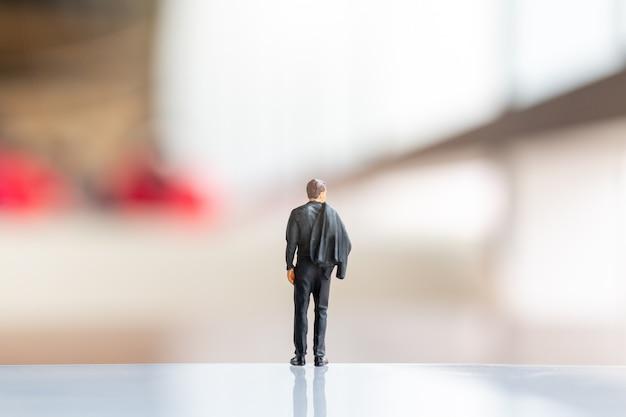 Miniatuurmensen: zakenman die zich op lege ruimte voor tekst bevindt