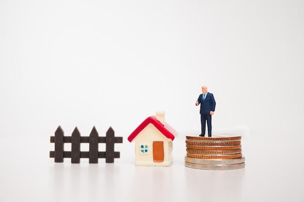 Miniatuurmensen, zakenman die zich op muntstukken met minishuis bevinden die als bedrijfsconcept gebruiken