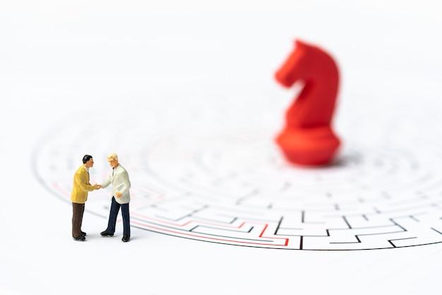 Miniatuurmensen, zakenman en schaakstukken in het labyrint of doolhof die de weg naar buiten vinden.