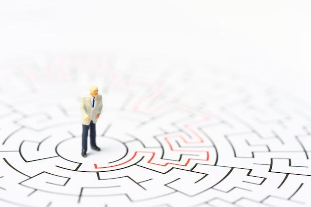 Miniatuurmensen, zakenman in het labyrint of doolhof die de uitweg berekenen.
