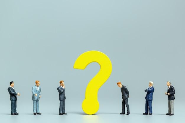 Miniatuurmensen, zakenman met grote vraag. arbeiders die het probleemconcept proberen op te lossen