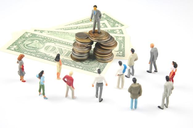 Miniatuurmensen. zakenman staat in de buurt van dollargeld. investeringen en inkomsten voor werk