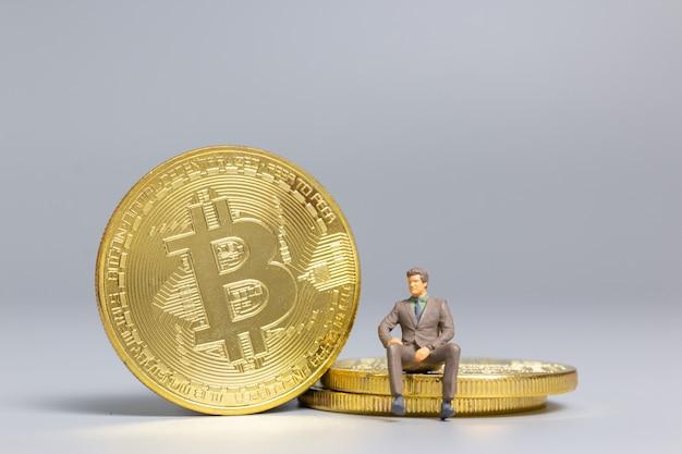 Miniatuurmensen zakenman zittend op bitcoin-munten