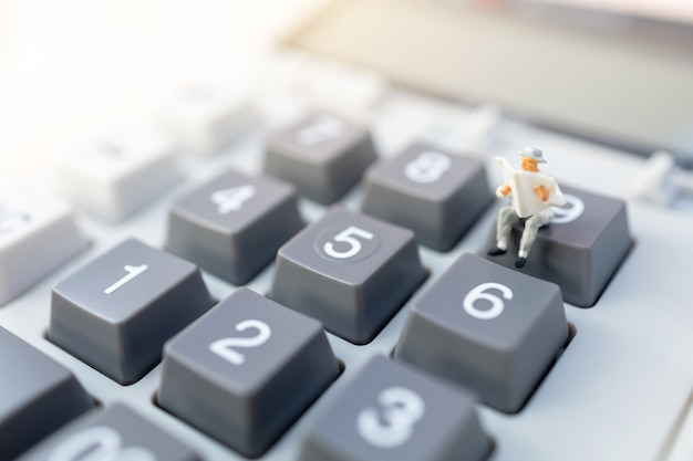 Miniatuurmensen: zakenmanlezing op calculator. financieel en bedrijfsconcept