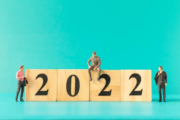 Miniatuurmensen: zakenmensen die op houten bloknummer 2022 staan, gelukkig nieuwjaarsconcept