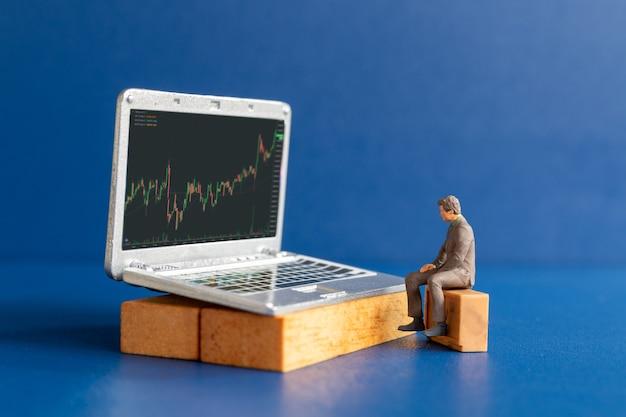 Miniatuurmensen, zakenmensen en laptop met aandelentickers, beurs- of forexhandelgrafiek in grafisch concept