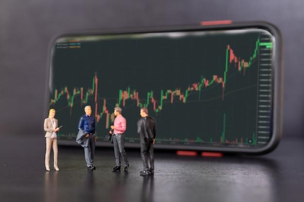 Miniatuurmensen, zakenmensen en smartphone met aandelentickers, beurs- of forexhandelgrafiek in grafisch concept