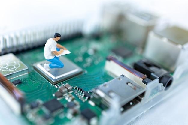 Miniatuurmensen zoeken of controleren op bugs en probleem op microchip, moederbord van computer.