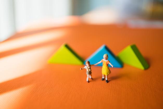 Miniatuurmensen, zuster en jonge broer die op tangram-raadselachtergrond lopen die als onderwijs en familieconcept gebruiken