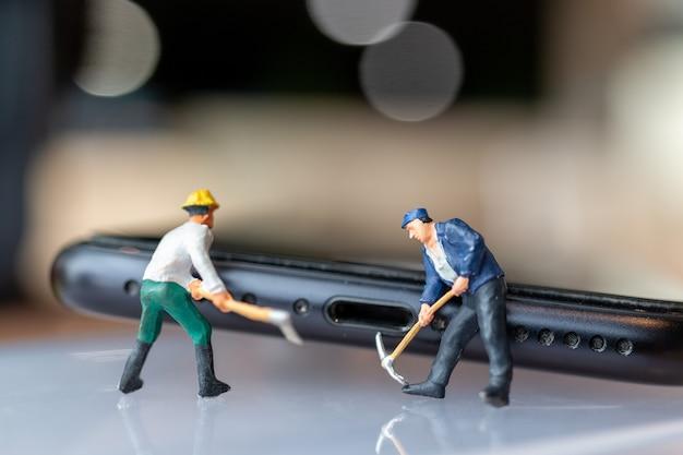 Miniatuurmensenarbeider met hulpmiddelen die mobiele telefoon, elektronisch apparatenconcept herstellen