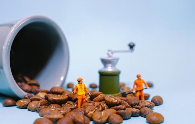 Miniatuurmensenarbeider op koffiebonen met kop en molenmachine, voedsel en drankconcept