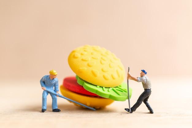 Miniatuurmensenarbeiders maken een concept voor hamburger, fastfood en junkfood.