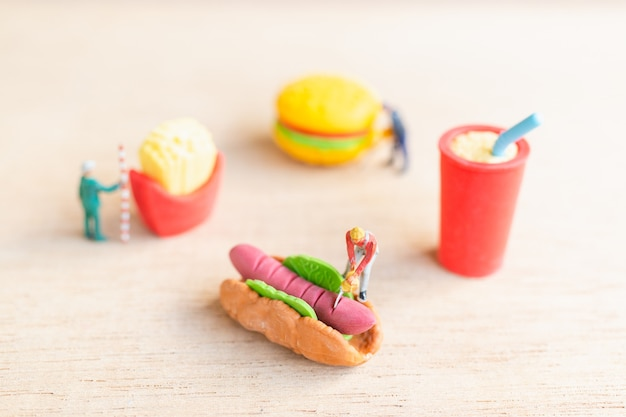 Miniatuurmensenarbeiders maken hotdogbroodjes, fastfood en junkfoodconcept.