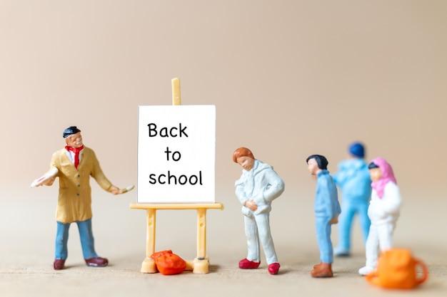 Miniatuurmensenleraar en studenten dichtbij canvas op schildersezel met het woord terug naar school
