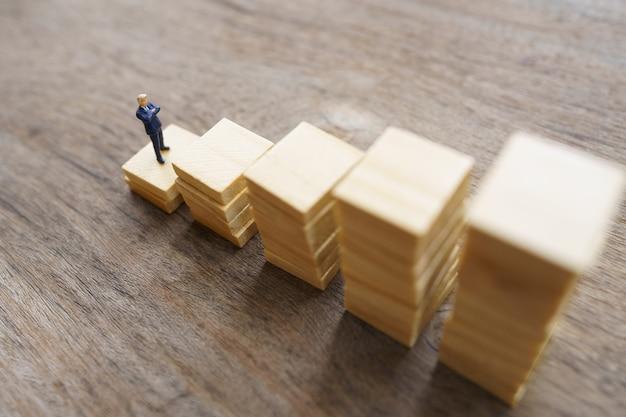 Miniatuurmensenzakenlieden die investeringsanalyse of investering bevinden zich. het concept van zijn