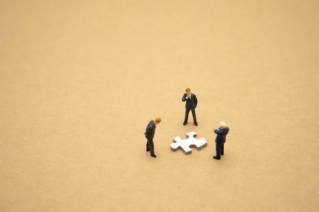 Miniatuurmensenzakenlieden die zich op witte figuurzaag bevinden.