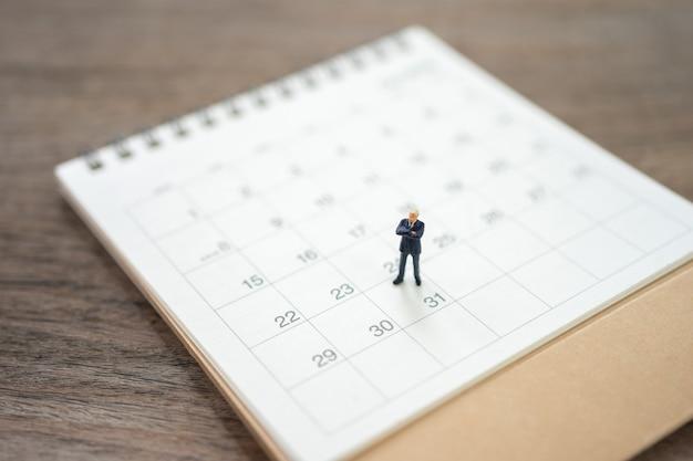 Miniatuurmensenzakenlieden die zich op witte kalender bevinden die als achtergrond bedrijfsconcept gebruiken