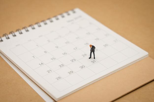 Miniatuurmensenzakenlieden die zich op witte kalender bevinden die als achtergrond gebruiken