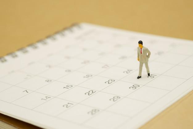 Miniatuurmensenzakenlieden die zich op witte kalender bevinden