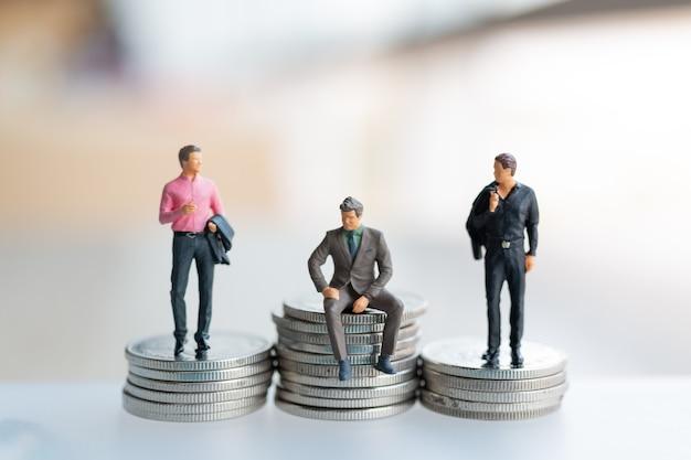 Miniatuurmensenzakenman met muntstukken. bedrijfsgroei concept