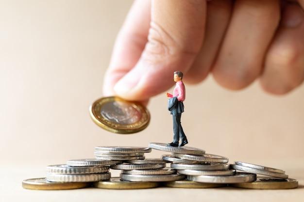 Miniatuurmensenzakenman met muntstukken. bedrijfsgroeiconcept