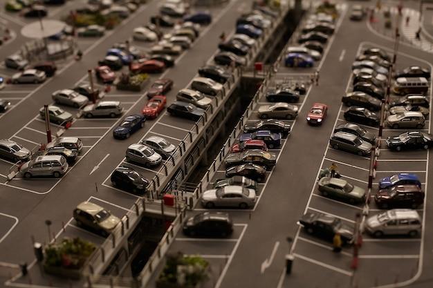 Miniatuurmodellen stellen auto's en vrachtwagens voor op de parkeerplaats van de grote stad