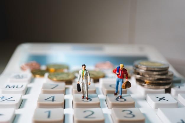 Miniatuurpaarzakenman die zich op calculator met stapelmuntstukken bevinden die als zaken en financieel concept gebruiken