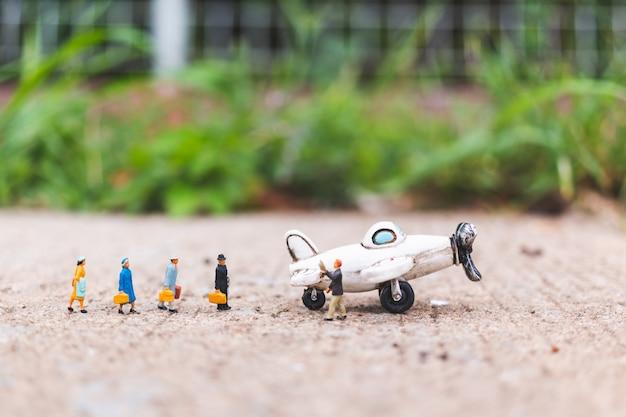 Miniatuurpersonen: reizende reizigers handbagage stap in het vliegtuig