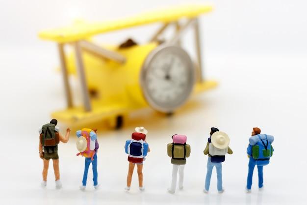 Miniatuurreiziger: backpacker met vliegtuig, reis en bedrijfsconcept.
