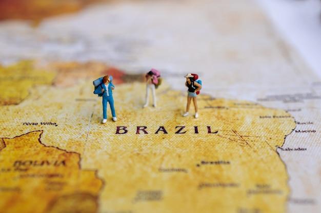 Miniatuurreiziger met een rugzak die zich op wereldkaart bevindt. reis concept.