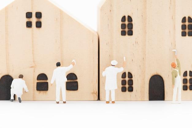 Miniatuurschilder schildert het model houten huis.