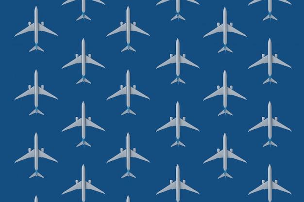 Miniatuurstuk speelgoed vliegtuig op blauwe pantoneachtergrond.