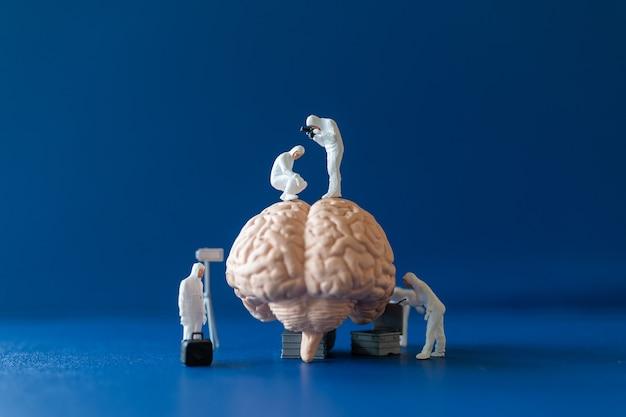 Miniatuurwetenschapper die een groot menselijk brein observeert en repareert op een blauwe achtergrond
