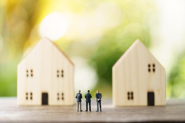Miniatuurzakenlieden staan investeringsanalyse huisvesting of investeringen