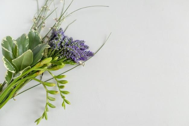Miniboeket van blauwe bloemen op een witte achtergrond.