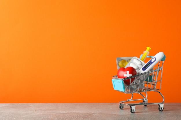 Miniboodschappenwagentje met medische uitrustingen op oranje achtergrond, ruimte voor tekst