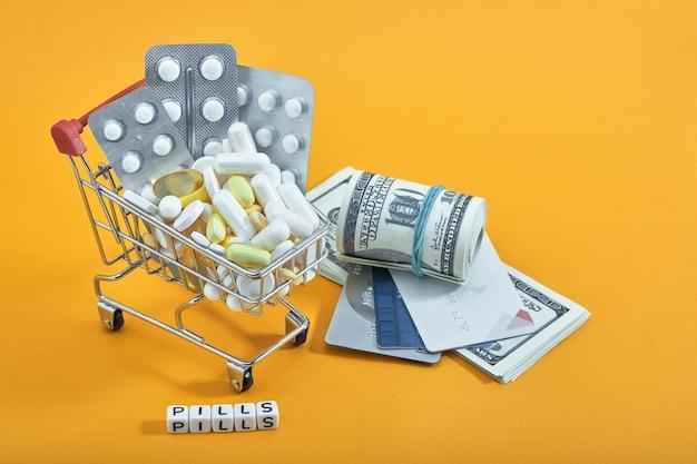 Miniboodschappenwagentje, pillen en capsules op gele lijst. farmaceutische industrie epidemie, pijnstillers, gezondheidszorg en behandelingsconcept