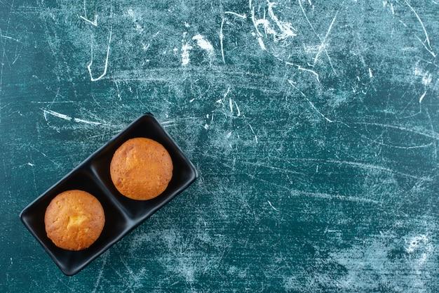 Minicakes in een schaal, op de blauwe tafel.
