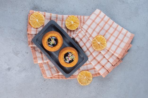 Minicakes met gelei en fruitplakken op steen.