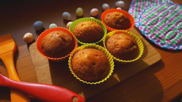 Minicakes versierd met eieren, pasen-dessert. simpele mini muffins in kleurrijke siliconen bakvormen. keuken en kookconcept op houten achtergrond