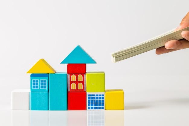 Minihuis met geld, spaargeld voor het kopen van een huis en lening aan bedrijfsinvesteringen voor onroerend goed concept.