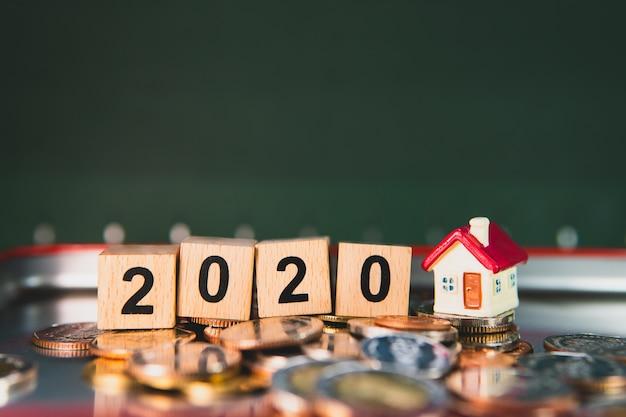 Minihuis met houten blokjaar 2020 en stapelmuntstukken die als bedrijfs financieel en bezit onroerende goederenconcept gebruiken