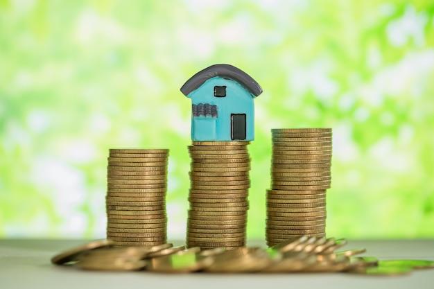 Minihuis op stapel muntstukken met groen onduidelijk beeld.