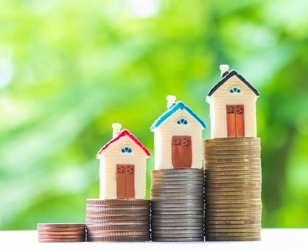 Minihuis op stapel muntstukken op een aard. concept van vastgoedbeleggingen, onroerend goed, geld besparen.
