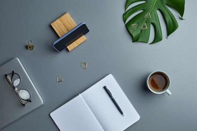 Minimaal bovenaanzicht plat leggen van tropisch blad en zakelijke accessoires over grijze werkplek achtergrond,