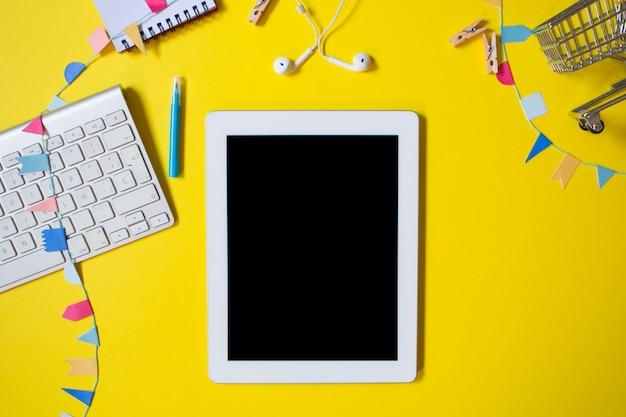 Minimaal bovenaanzicht van een jeugdtafel met laptop, toetsenbord, notebook, pen en enkele kleine wasknijpers. freelancer werkplek op geel