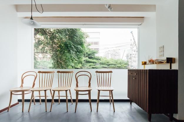 Minimaal broodcafé versieren met witte muur en houten stoelen.