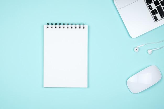 Minimaal bureau met laptop en blanco notitieblok pagina