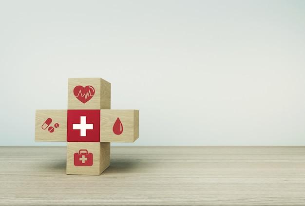 Minimaal conceptidee over van gezondheid en medische verzekering, die houtsnedestapelen schikken met pictogramgezondheidszorg medisch op lijstachtergrond.